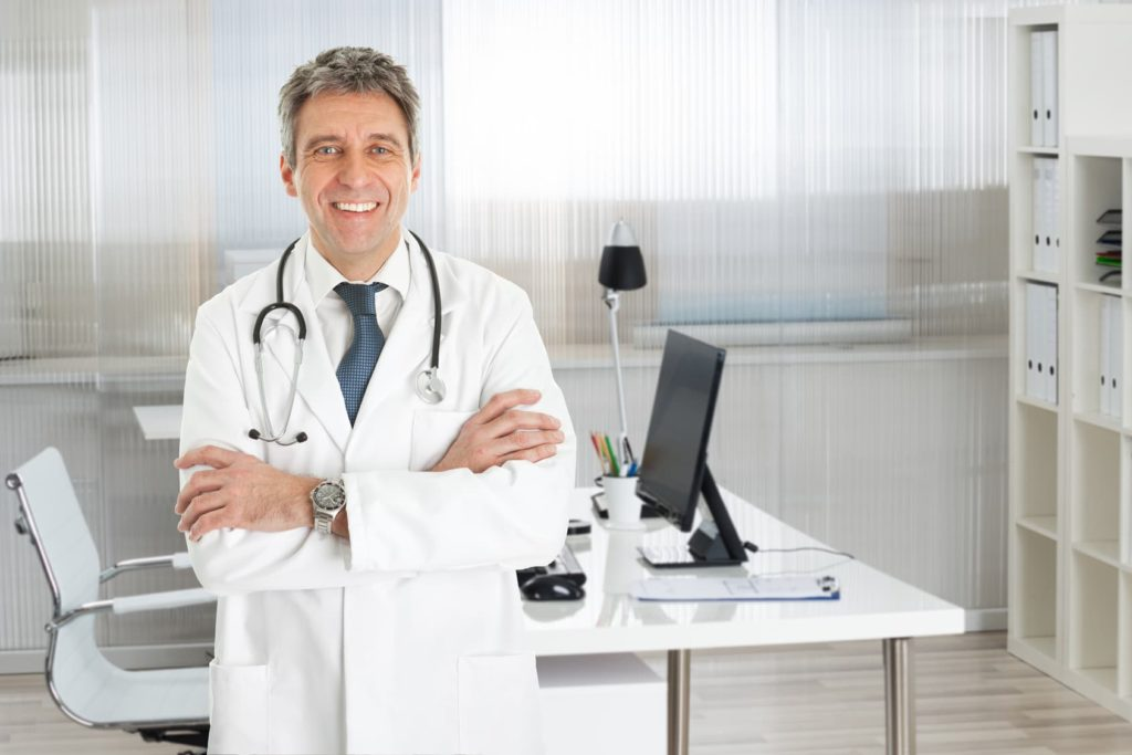 Confident Male Doctor Standing Arms Crossed In Clinic
