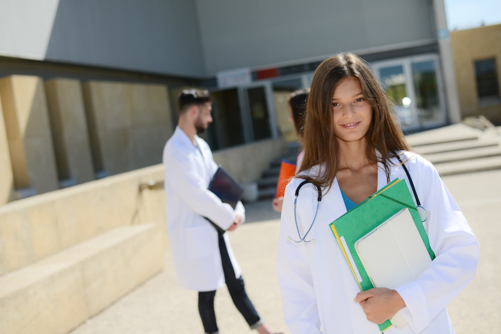 portrait of attractive cheerful young medical student woman outdoor in front of hospital university campus