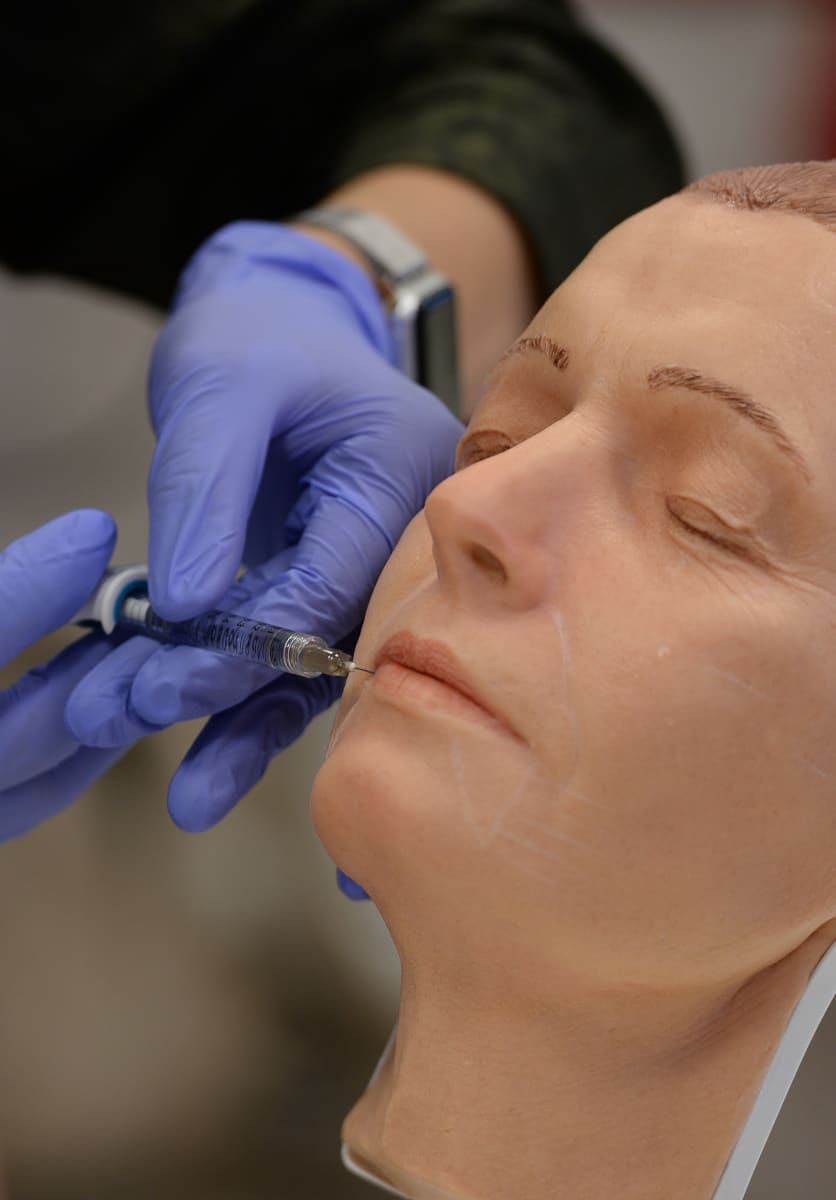 A student on our Foundation Training in Botox & Dermal Fillers practices lip filler on one of our high fidelity mannequins.